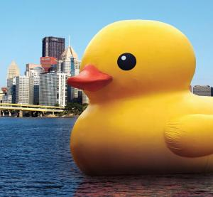 The 40 foot rubber duck floating on the Allegheny river with the city skyline in the background.